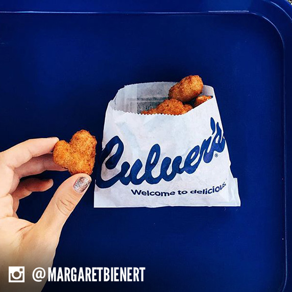 Culver's guest holding a Cheese Curd heart alongside a bag full of Culver's Wisconsin Cheese Curds.