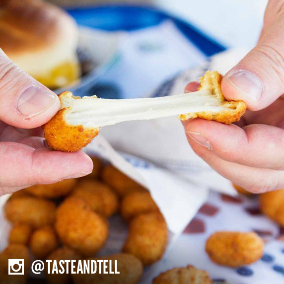 Culver's guest pulling apart a Wisconsin Cheese Curd to see how far they can pull it before it breaks into two pieces.