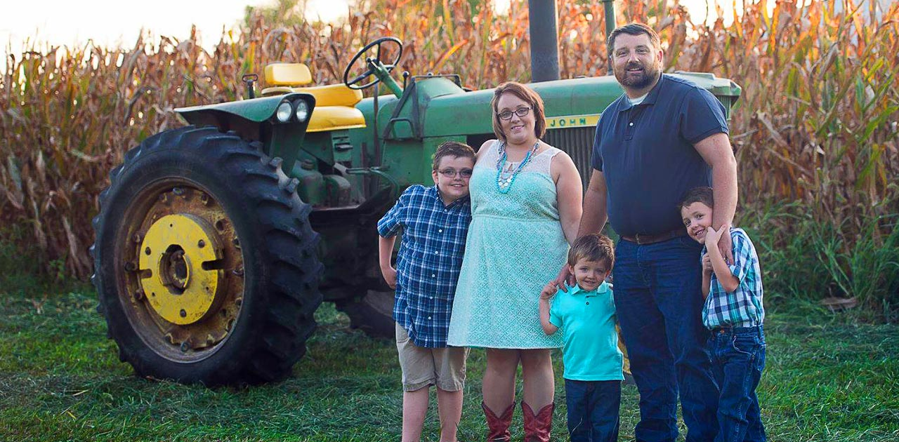 Christopher and Elizabeth with their three kids posing in front of their tractor and corn field
