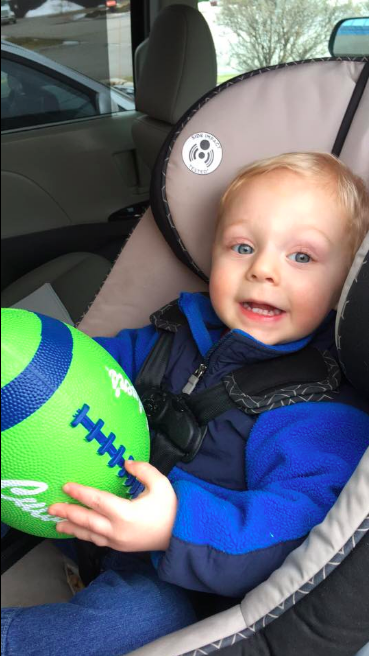 A toddler smiling in a car seat while holding a green Culver's football