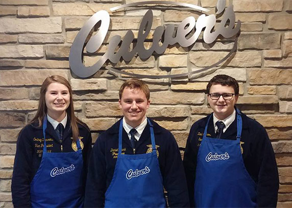 Three FFA members stand in front of a Culver's sign in their blue jackets and Culver's aprons.