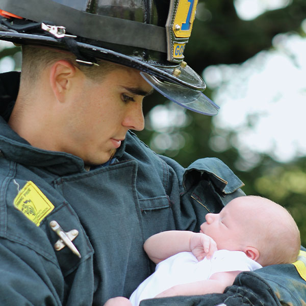 Firefighter Hero - Photograph of firefighter hold a baby.