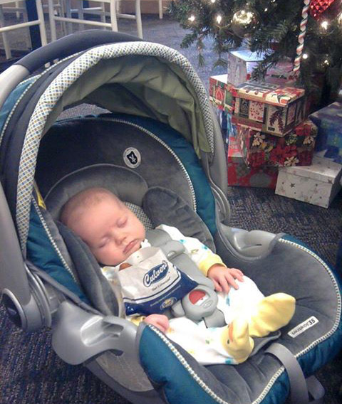 Baby Hanalei sleeps next to an order of Cheese Curds in a carrier at Culver's and a Christmas tree in the background.