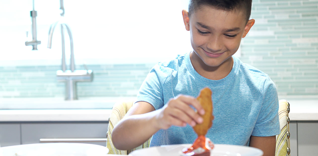 Kid dunking a Chicken Tender