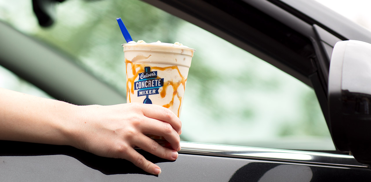 A hand coming out of a car window holding a caramel concrete mixer with marbled caramel on the inside