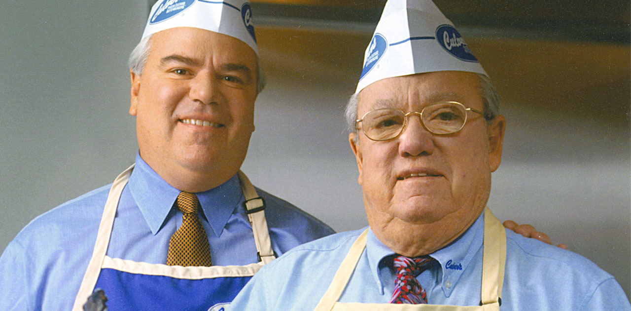 Image of founder Craig Culver and his dad and co-founder George Culver dressed in aprons ready to cook.