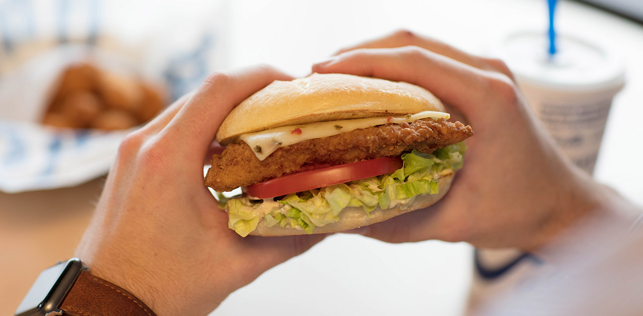 A guest holds a Crispy Southwest Chicken Sandwich