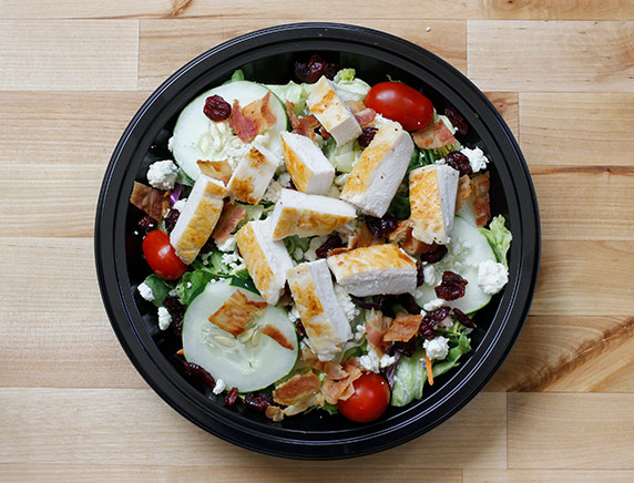 An aerial photo of Culver's Cranberry Bacon Bleu salad in a black bowl sitting on a wooden countertop