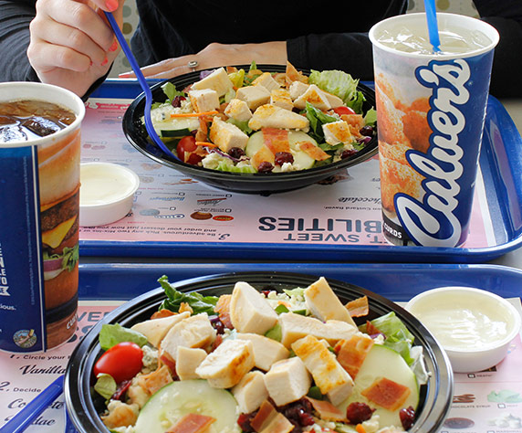 Two Culver's Cranberry Bacon Bleu salads with dressing on the side and regular drinks sitting on blue serving trays.