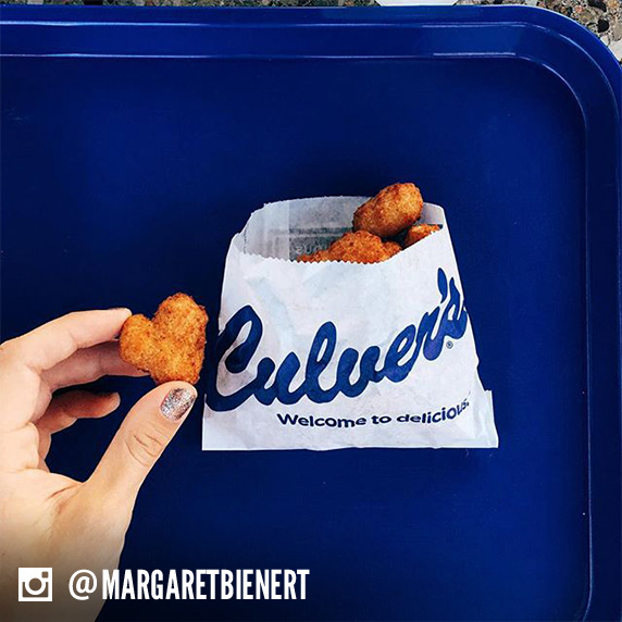 A woman holds a heart-shaped cheese curd over a Culver's tray