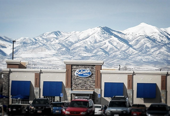 A photo of a Culver's restaurant taken from its parking lot with snowy mountaintops in the background