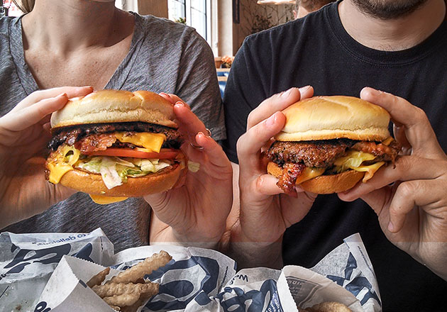Woman and Man smiling holding Culver's ButterBurger® in hands