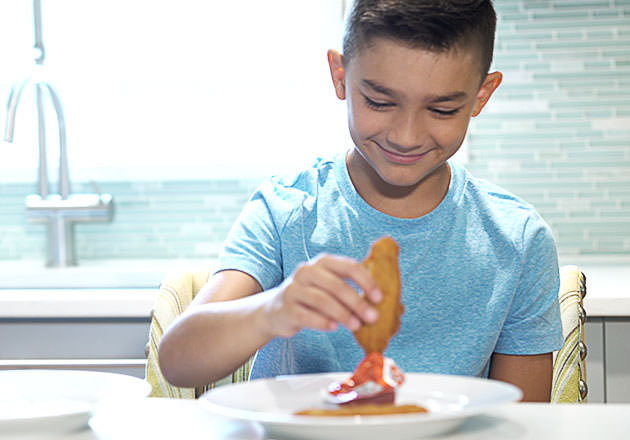 A boy sitting in a kitchen smiles while dunking a chicken tender into ketchup