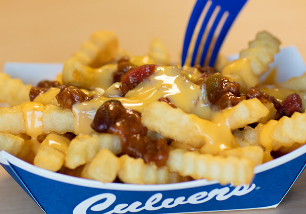 Two forks dig into Culver's Chili Cheddar Fries in paper tray on wooden table
