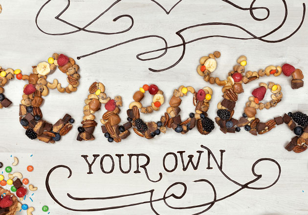 "A variety of candy and fruit toppings arranged to spell ""Create Your Own."""