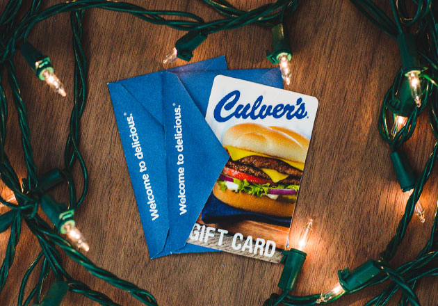 Woman sitting by a fire opening a card with a Culver's Gift Card inside