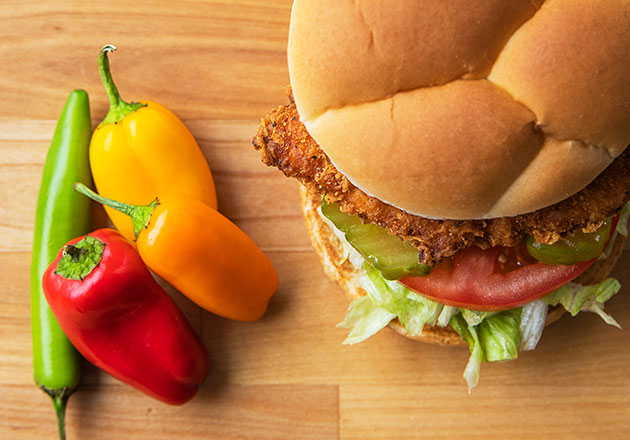 The Spicy Crispy Chicken Sandwich sits next to four peppers on a wood table.