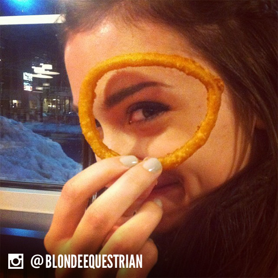 A woman holds an Onion Ring up to her face and looks through it.