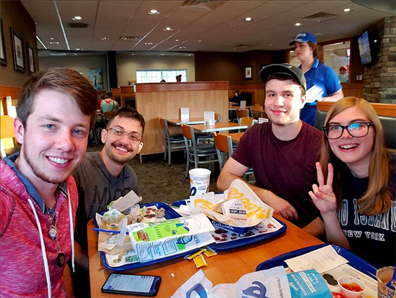 Four friends sit around a table at Culver's, smiling for the camera.
