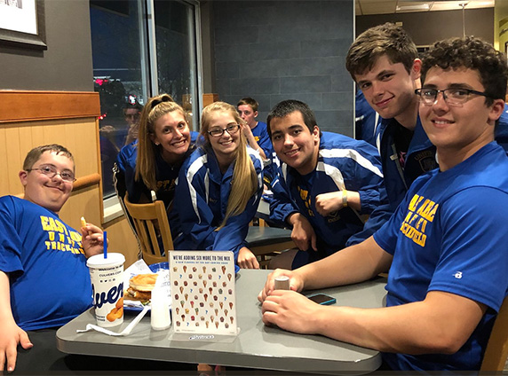 Six teammates in blue uniforms enjoy their visit to Culver's.