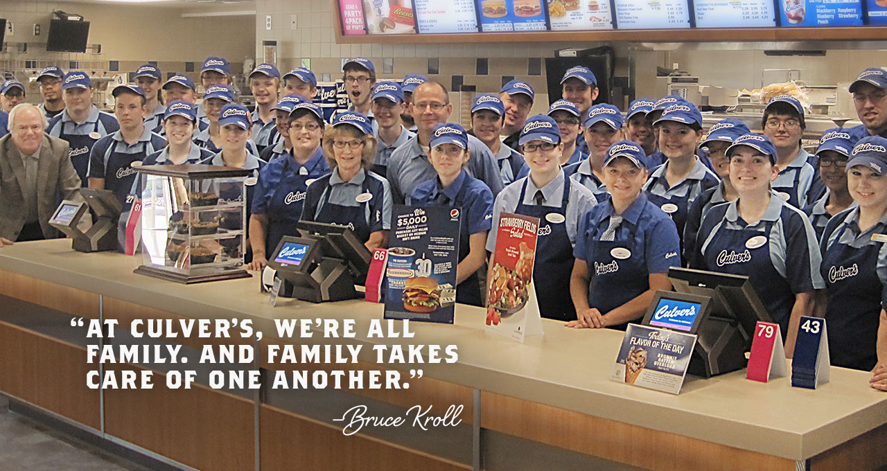 Entire Restaurant team stands behind the order counter all facing camera. Text: at Culver's we're all family, and family takes care of one another