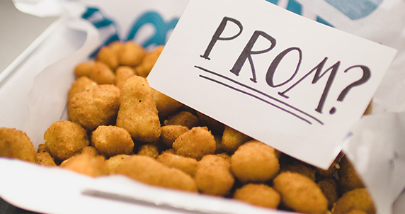 "A note that reads ""Prom?"" sits inside a family-size order of Cheese Curds."