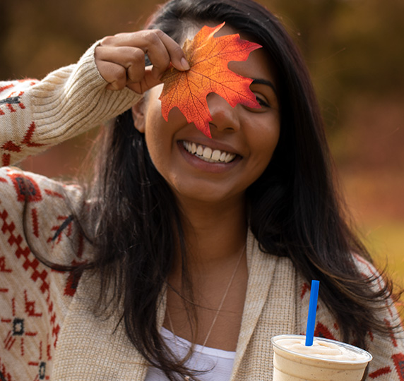 Photo of person holding a leaf to face while smiling and holding a Pumpkin Spice Shake.