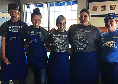 FFA members stand in a restaurant in Culver's aprons and FFA t-shirts.