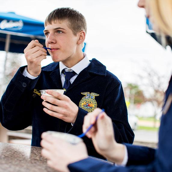 FFA member in his blue jacket takes a bite of Fresh Frozen Custard