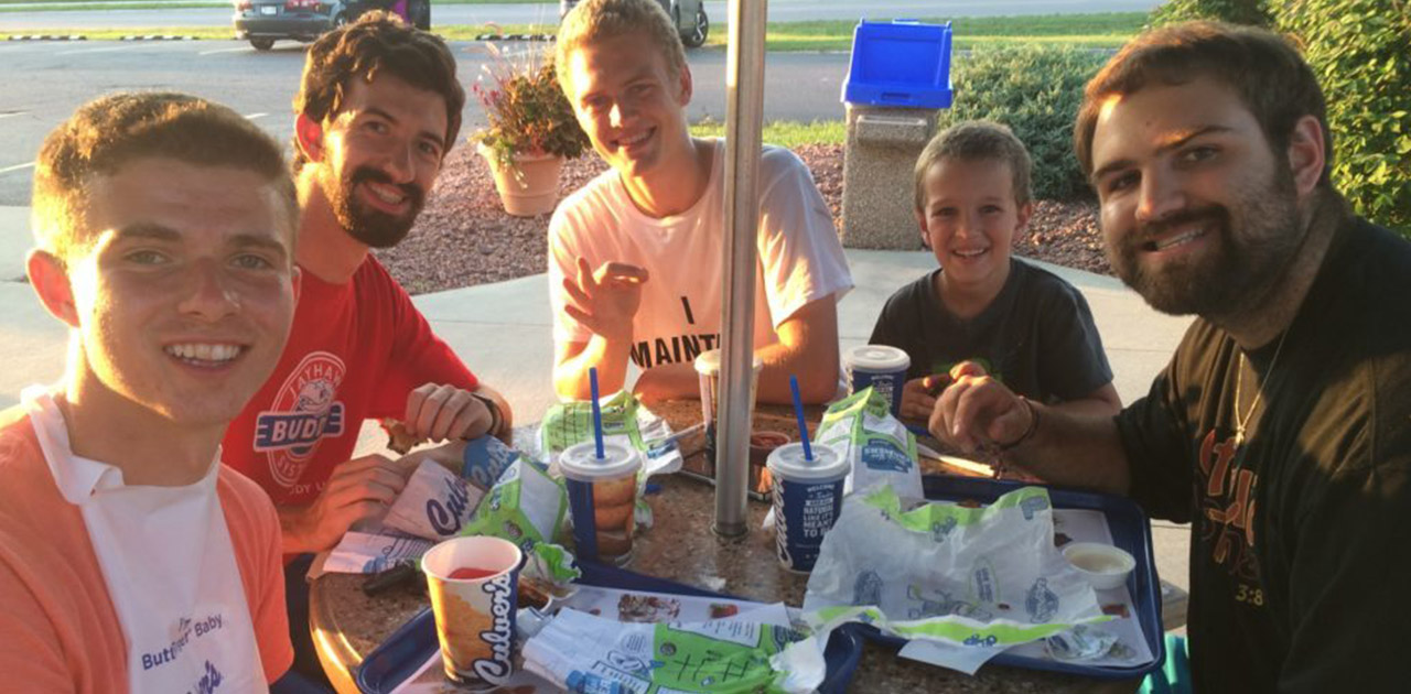 Camp attendees sitting outside on Culver's patio in group with Kids' Meals on table