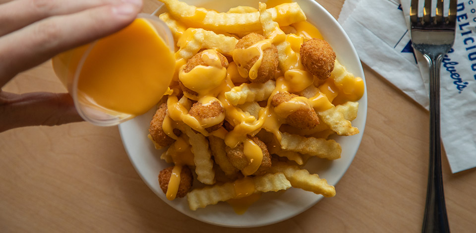 person drizzles cheese sauce over a container of crinkle cut fries and cheese curds