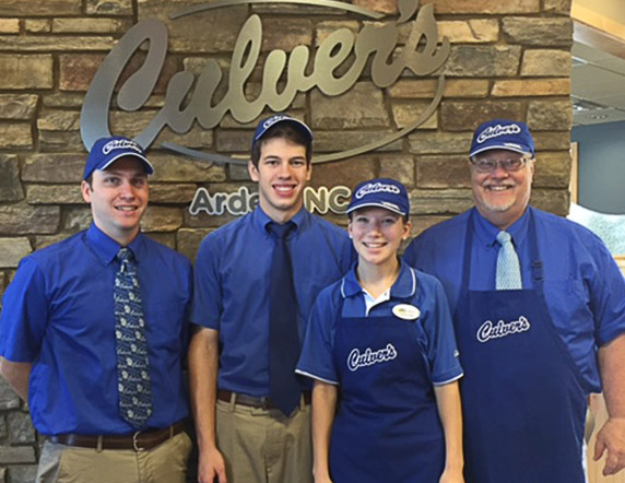 Kraig and Tom Tabor with two other family member standing in uniform in front of inside Culver's sign.