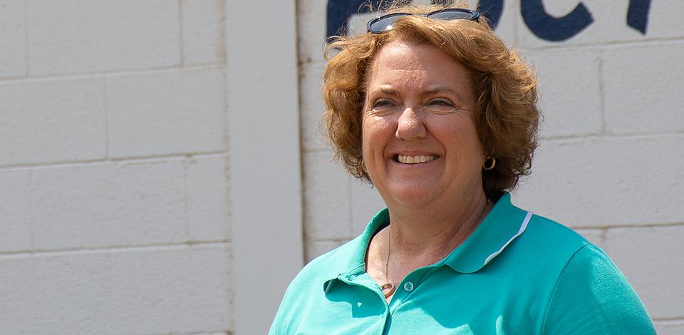 NCBA President Jennifer Houston poses in front of a livestock barn.