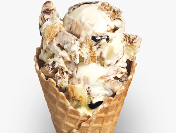 Strings of chocolate syrup and crumbles of fluffy puff pastry are mixed into vanilla frozen custard and served in a sugar cone