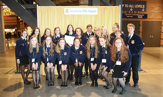 FFA members in front of American FFA Degrees sign.