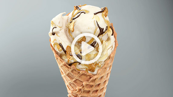 The New Chocolate Pretzel Crunch Flavor of the Day in a cone with a grey background