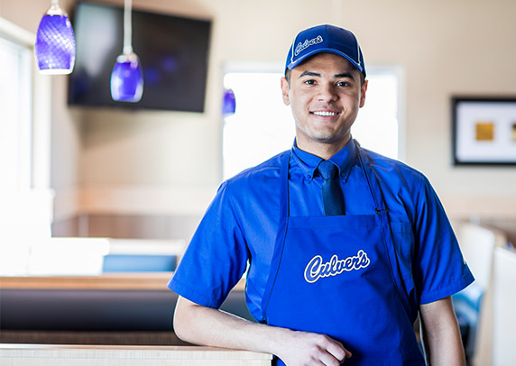 Ethan in his True Blue Crew uniform and smiling in a Culver's restaurant.