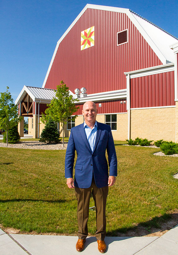 Culver's CEO Joe Koss stands in front of the Farm Wisconsin Discovery Center