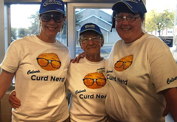 Sharon stands in the restaurant with two team members, wearing Curd Nerd shirts.