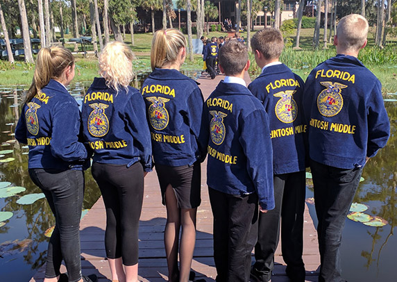 A group of FFA members stand on a dock with their backs to the camera, showing off their blue jackets
