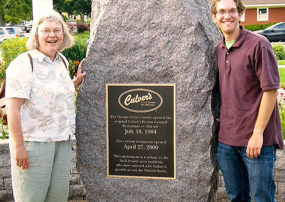 Jane and her son Eddie pose in front of a historical marker at the Culver's of Sauk City, WI.