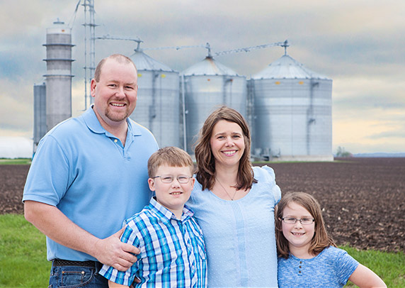 Katie Pratt with her family standing in front of her farm.