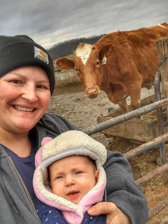 Marie and her baby daughter Millie take a selfie with a cow.