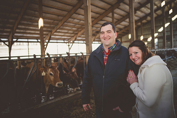 Marie and Rick pose with cows in a barn.