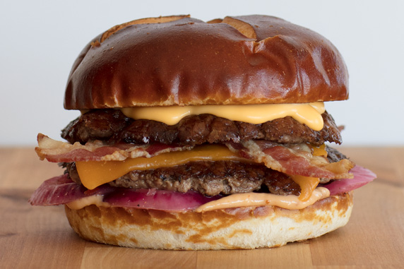 The Pretzel Haus Pub Burger sits on a wood board in front of a white background