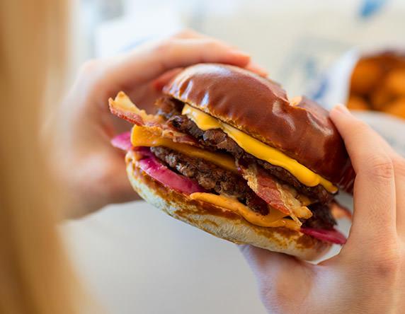 A woman holds a Pretzel Haus Pub Burger, preparing to take a bite.
