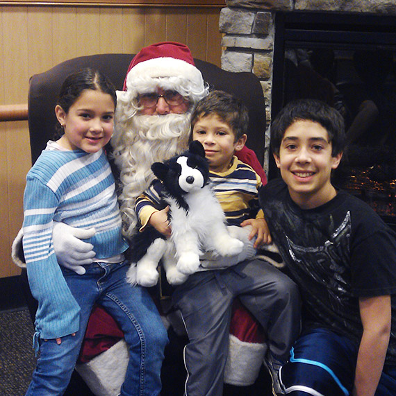 Three kids sitting on and standing next to Santa at Culver's.