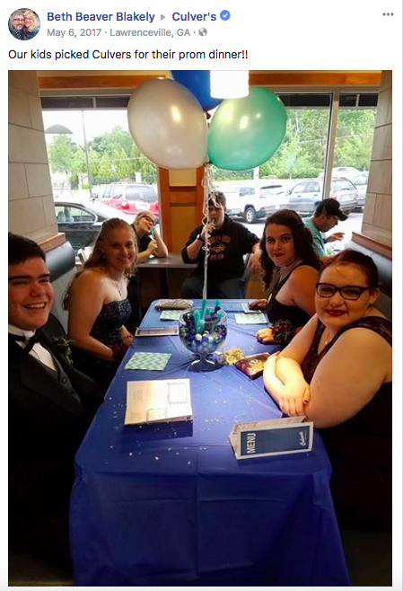 A group of high schoolers enjoy a pre-prom dinner at Culver's with balloons and a blue tablecloth.
