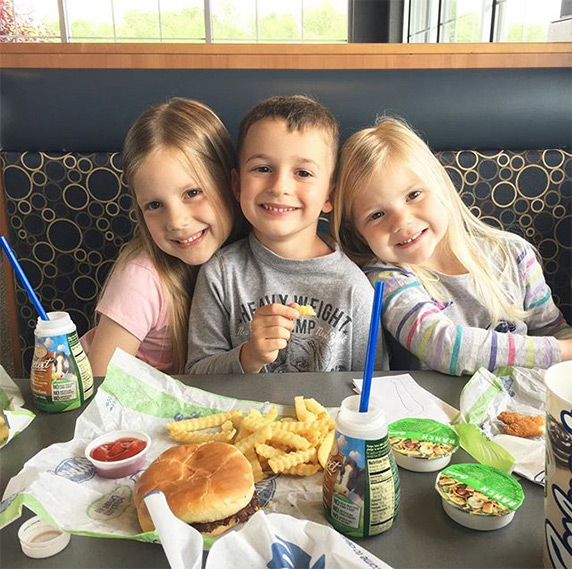 Three kids sitting in Culver's restaurant booth eating ButterBurger® and kids' meals