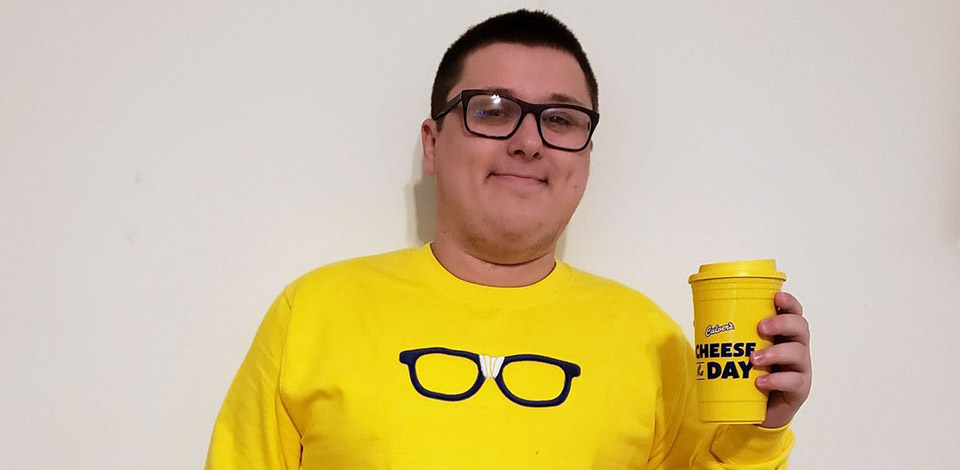 "Kurtis Culver wearing a yellow Curd Nerd sweatshirt with black framed glasses, and holding a ""Cheese the Day"" yellow travel mug"